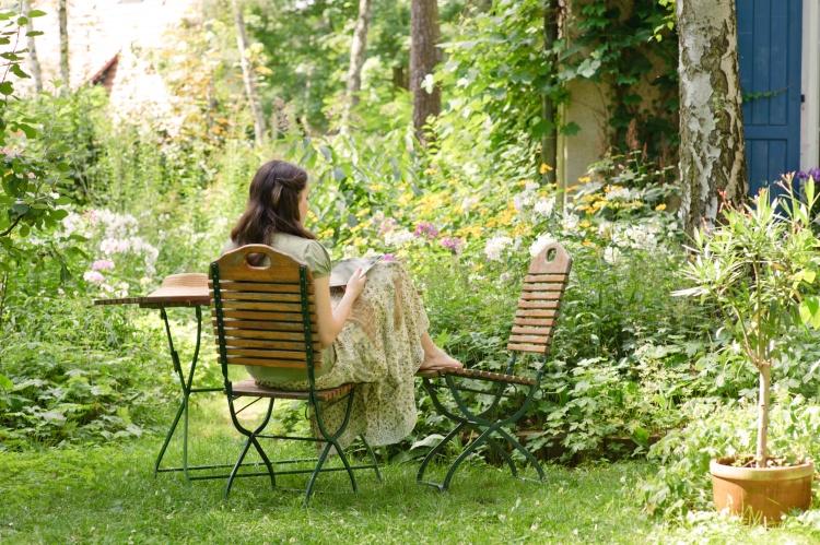 Junge Frau im Garten ließt ein Buch